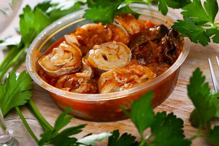 Piquant marinated rolls of Baltic herring fillet in tomato sauce with mushrooms. Popular polish hunting style fish appetizer