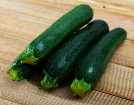 Closeup of fresh zucchinis on wooden surface. Healthy vegetarian ingredient