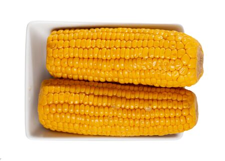 Cobs of freshly boiled corn served on white plate. Tasty vegetarian snack. Isolated over white background