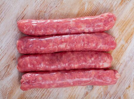 Raw farm sausages with rosemary on wooden table