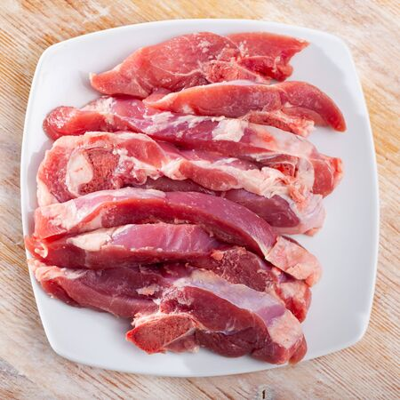 White plate with sliced fresh raw turkey thigh on wooden background