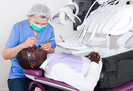 Dentist is treating male patient which is sitting in dental chair  Фото со стока
