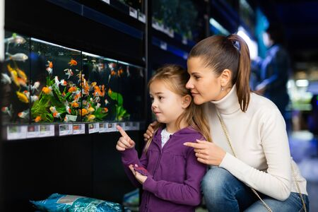 Happy little girl with mother choosing new aquarium fish for home fish tank in pet store