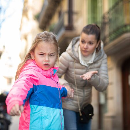 Portrait of angry naughty little girl in colorful jacket while walking outdoors with worried young mother