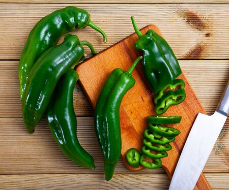 Closeup of chopped organic green sweet pepper on wooden background. Healthy nutrition concept Banco de Imagens