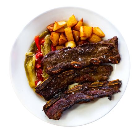 Appetizing grilled beef ribs served on white plate with fried potatoes and baked bell pepper. . Isolated over white background