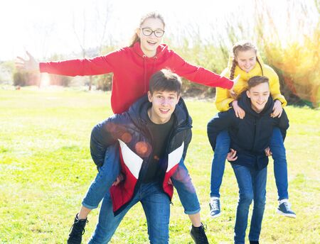 Group of laughing teenagers spending time together on spring day, girls riding piggy-back on boys. Concept of happy adolescence