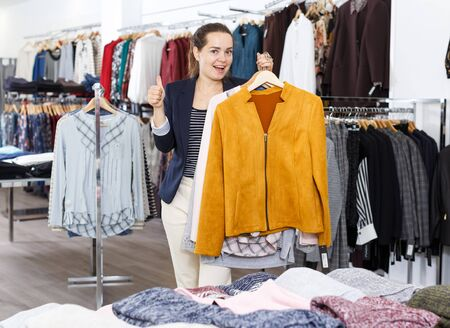 Young cheerful woman demonstrating clothes on hangers in clothing boutique