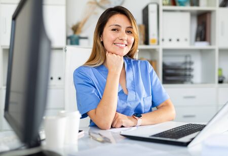 Portrait of latino female doctor working on laptop consulting patient online, telemedicine concept