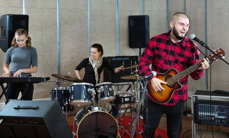 Bearded guy soloist playing a guitar and singing with two girls of his music band in studio