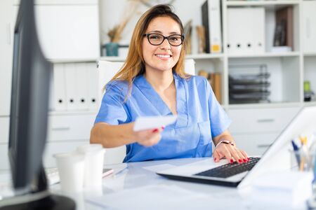 Hispanic female doctor working with patient in medical office giving prescription