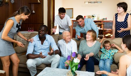 Big family with grandparents spending time together in living room
