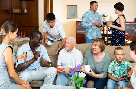 Portrait of big multigenerational family chatting on sofa at home