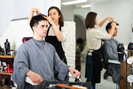 Female hairdresser making hair styling for young man, working day in beauty salon
