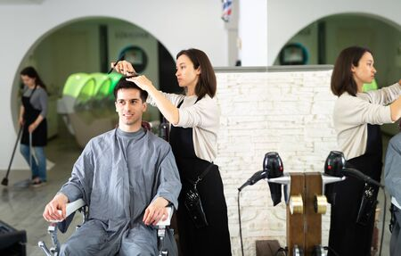 Portrait of female hairdresser and male client getting haircut at local hair studio