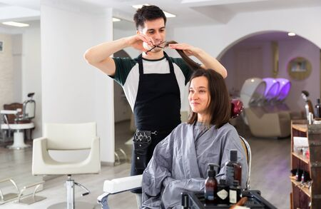 Portrait of male hairdresser and female client getting haircut at local hair studio Stock fotó - 148183606