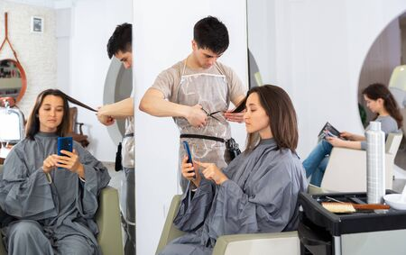 Positive male hairdresser making hair styling for young woman, woman using mobile phone Stock fotó