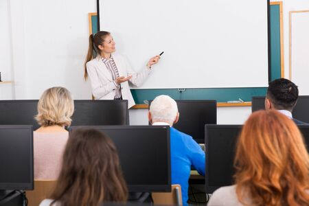 Friendly young female teacher lecturing attentive adult students of different ages in computer room Banque d'images