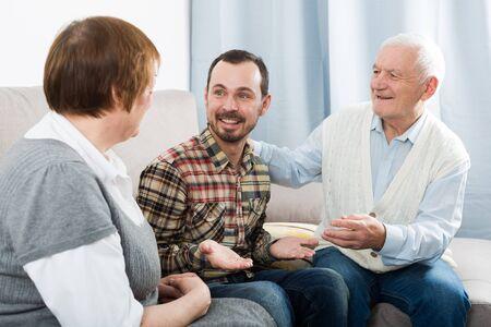 Elderly grandparents friendly conversation with grandson sitting on sofa Banque d'images