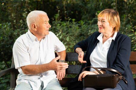 Elderly couple talking emotionally sitting on bench in park on sunny day Reklamní fotografie