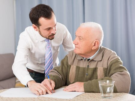 Elderly man and employee of social department is filled with form