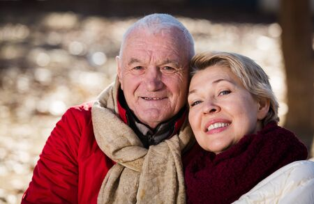 Aged husband and wife sitting together on bench in park on chilly day Imagens