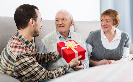 Adult son handing gifts to senior parents during evening together at home