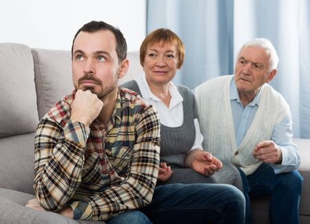Old grandparents talking seriously with grandson and solve family problems