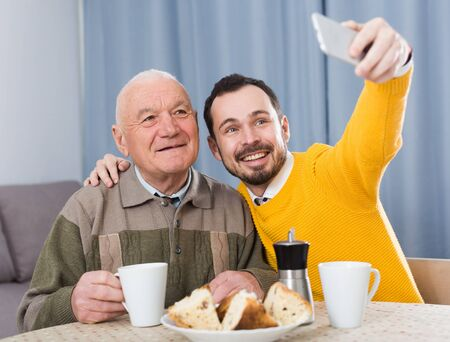 Father and adult son taking photos together at home Imagens - 148271101