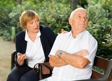 Senior man sitting turned away from elderly apologizing woman on bench in park