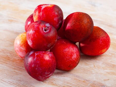 Whole ripe organic red plums on wooden table. Healthy vitamin product Banco de Imagens