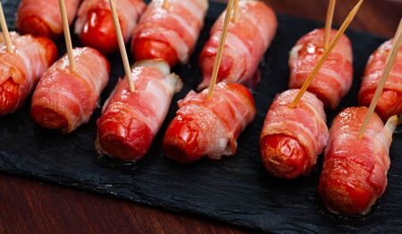 Appetizing grilled bacon wrapped little sausages served with red wine