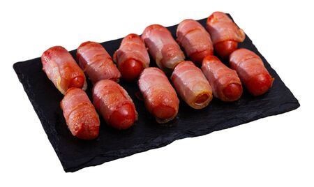 Roasted miniature sausage links wrapped in smoky bacon. Tasty appetizer for wine. Isolated over white background