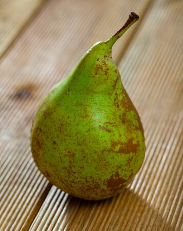 Closeup of fresh ripe green pear on wooden surface. Organic fruits concept