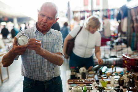 Loving senior family couple choosing vintage things on street market