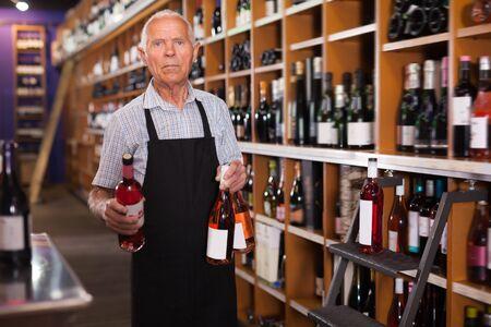 Mature male vintner working in modern wine shop, arranging wine bottles on racks Stock Photo