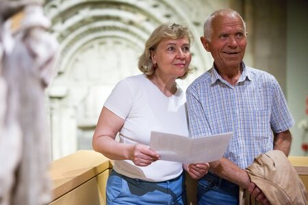 Positive elderly man and woman with guidebook standing at hall of Art Museum