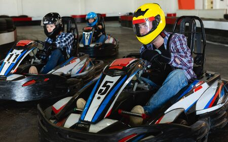 Young positive people driving sport cars for karting in a circuit lap in sport club Stockfoto