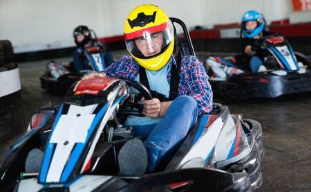 Portrait of happy  positive smiling male racer in helmet driving kart on track 免版税图像
