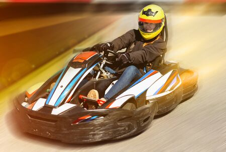 Glad cheerful positive woman driving sport car for karting in a circuit lap outdoor in sport club