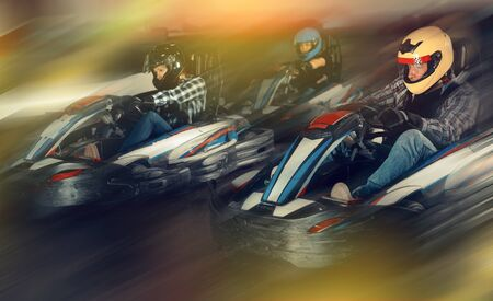 Young positive people in helmets driving racing cars for karting in sport club