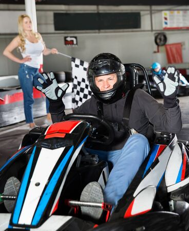 Portrait of male racer in helmet crossing a finish line on kart track