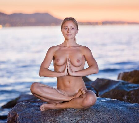 Nude woman 25-35 years old is sitting on a rock near the sea at dawn 스톡 콘텐츠