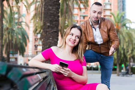 Young woman is inaccessibility when man is playful talking with her in the park.