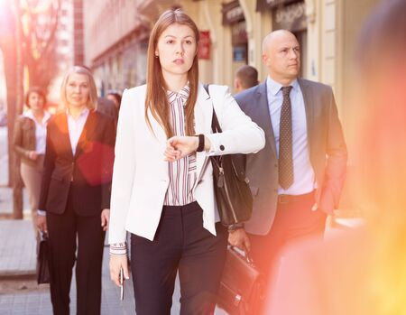 Confident elegant young businesswoman walking on city street, checking time on her watch