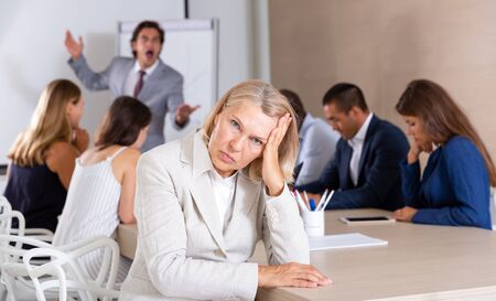 Upset adult business woman on meeting with colleagues and angry boss
