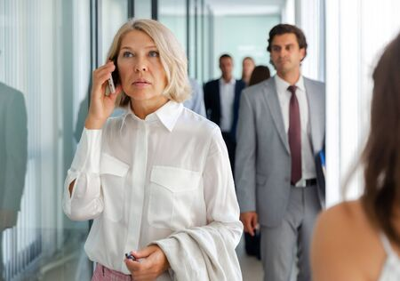 Portrait of adult business woman talking on mobile phone in office