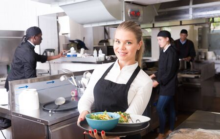 Successful young waitress standing in restaurant kitchen with ordered meals, ready to serving guests