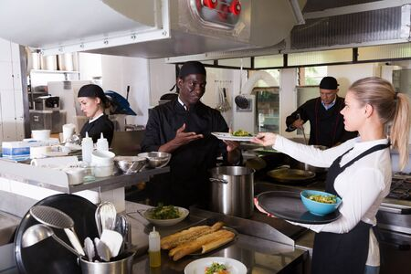 African-American chef of restaurant giving to waitress cooked dish ready to serving