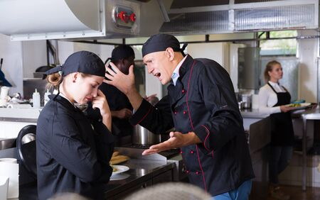 Angry male chef talking to his female assistant in commercial kitchen